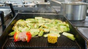 Vegetal fuming fritado na grade em um fundo obscuro da cozinha do restaurante Pimenta, abobrinha faixa da carne, milho filme
