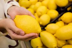 Vegetariërs en vers fruit en groenten op de aard van het thema: menselijke hand die een citroen houden royalty-vrije stock foto's