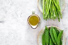 vegetarian еды здоровый Спаржа и горох около кувшина масла на сером каменном copyspace взгляд сверху предпосылки Стоковое Изображение