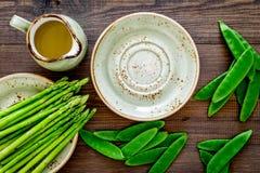 vegetarian еды здоровый Спаржа и горох около кувшина масла на темном деревянном взгляд сверху предпосылки Стоковые Фото