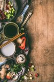 Vegetarian asian cooking ingredients with chopsticks, coconut milk, soy sauce, chopped spices and vegetables on rustic wooden Royalty Free Stock Photography