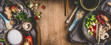 Vegetarian Asian cuisine ingredients for stir fry with chopped vegetables, coco milk, spices,chopsticks and wok pot on rustic wood Royalty Free Stock Images