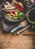 Vegetarian Asian cuisine ingredients for stir fry in wok pot with chopped vegetables, soy sauce , spices and chopsticks on rustic Royalty Free Stock Images
