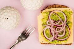 Vegetarian Avocado and Jarisberg Cheese Rye Bread Open Faced San. Dwich With Sliced Onions Against A Lilac Background Royalty Free Stock Photo