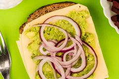 Vegetarian Avocado and Jarisberg Cheese Rye Bread Open Faced San. Dwich With Sliced Onions Against A Green Background Stock Image