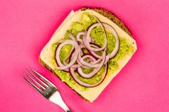 Vegetarian Avocado and Jarisberg Cheese Rye Bread Open Faced San. Dwich With Sliced Onions Against A Pink Background Stock Photos