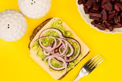 Vegetarian Avocado and Jarisberg Cheese Rye Bread Open Faced San. Dwich With Sliced Onions Against A Yellow Background Royalty Free Stock Photos