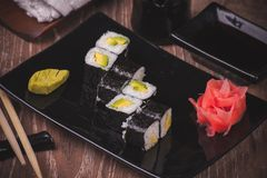 Vegetarian avocado sushi roll on black plate Royalty Free Stock Images