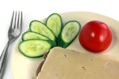 Vegetarian breakfast. Sandwich with cheese, the tomato and a cucumber lie on a plate Royalty Free Stock Photos