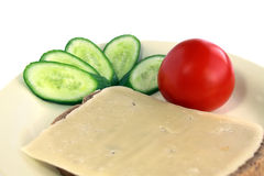 Vegetarian breakfast. Sandwich with cheese, the tomato and a cucumber lie on a plate Stock Photos