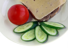 Vegetarian breakfast. Sandwich with cheese, the tomato and a cucumber lie on a plate Stock Images