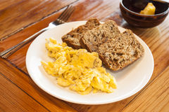 Vegetarian Breakfast of Eggs and Banana Bread. Plate of scrambled eggs and banana bread on a wooden table with a dish of butter royalty free stock images
