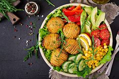 Vegetarian buddha bowl. Raw vegetables and baked potatoes in bowl. Vegetarian buddha bowl. Raw vegetables and baked potatoes in  bowl. Vegan meal. Healthy and Stock Photography