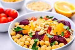 Vegetarian Bulgur Wheat and Quinoa Lunch Bowl. With Orange Segments, chickpeas, Beetroot and Tomatoes stock images
