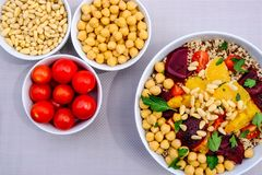 Vegetarian Bulgur Wheat and Quinoa Lunch Bowl. With Orange Segments, chickpeas, Beetroot and Tomatoes royalty free stock photo