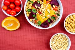 Vegetarian Bulgur Wheat and Quinoa Lunch Bowl. With Orange Segments, chickpeas, Beetroot and Tomatoes stock photo