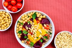 Vegetarian Bulgur Wheat and Quinoa Lunch Bowl. With Orange Segments, chickpeas, Beetroot and Tomatoes stock photos