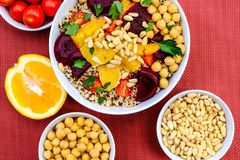 Vegetarian Bulgur Wheat and Quinoa Lunch Bowl. With Orange Segments, chickpeas, Beetroot and Tomatoes royalty free stock photos
