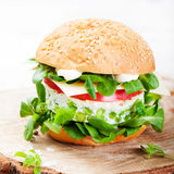 Vegetarian burger with egg and pea patty, fresh salad on a cutting wooden board Stock Photography