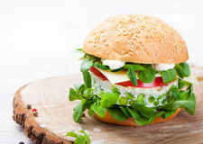 Vegetarian burger with egg and pea patty, fresh salad on a cutting wooden board Royalty Free Stock Images