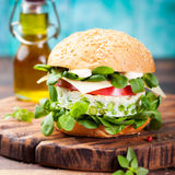 Vegetarian burger with egg and pea patty, fresh salad tomato. Royalty Free Stock Images