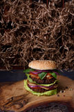 Vegetarian burger with falafel patty on rustic wooden board, hay straw texture background. Royalty Free Stock Images