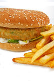 Vegetarian Burger and fries. Close up of a breadcrumbed vegetarian or veggie burger and fries, could also be used for chicken burger or fish burger Stock Photos