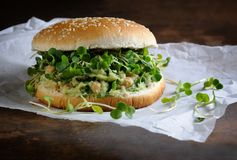 Vegan burger. A vegetarian burger made from a gluten-free bun with chickpeas, avocado and herbs, radish sprouts. A quick and healthy lunch idea that you feel Royalty Free Stock Photos