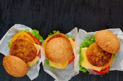 Vegetarian burgers with falafel, salad, onion, cheese, tomatoes on the black background. Traditional Middle Eastern fast food. Three vegetarian burgers with royalty free stock photos