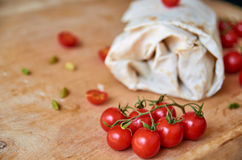 Vegetarian burrito with vegetables on blurred background. On foreground small cherry tomatoes on brown wooden background close up Royalty Free Stock Image