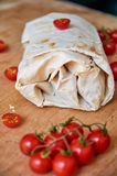 Vegetarian burrito with vegetables decorated with cardamom seeds on brown wooden background. On blurred foreground cherry tomatoes Royalty Free Stock Images