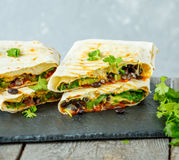 Vegetarian burritos wraps with beans, avocado and cheese on a slate
