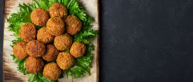 Vegetarian chickpeas falafel balls on wooden rustic board. Traditional Middle Eastern and arabian food. Dark background. Copy space royalty free stock photo