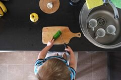 Vegetarian Child Cuts Green Cucumber With Knife In Kitchen, Vegan Kid Helper, Montessori Training, Top View Above Royalty Free Stock Photography