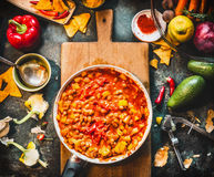 Vegetarian chili con carne dish in pan on wooden cutting board with spices and vegetables cooking ingredients on dark kitchen tabl Royalty Free Stock Photo