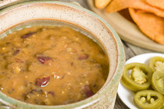 Vegetarian Chili. Chili made with soy protein and beans served with tortilla chips, pico de gallo, jalapenos, guacamole and sour cream Royalty Free Stock Photography