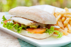 Vegetarian Ciabatta with tomatoes, grilled cheese haloumi, avocado and lettuce with french fries Royalty Free Stock Photo