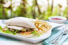 Vegetarian Ciabatta with tomatoes, grilled cheese haloumi, avocado and lettuce with french fries Royalty Free Stock Images