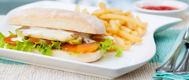 Vegetarian Ciabatta with tomatoes, grilled cheese haloumi, avocado and lettuce with french fries Royalty Free Stock Image