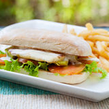 Vegetarian Ciabatta with tomatoes, grilled cheese haloumi, avocado and lettuce with french fries Royalty Free Stock Photos