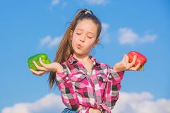 Vegetarian concept. Kid girl hold red and green peppers sky background. Child presenting kinds of pepper. Kid hold ripe. Pepper harvest. Fall harvest homegrown stock photography