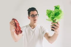 Vegetarian concept. Man offering a choice of meat or vegetables Salad leaves . Nerd is wearing glasses. Vegetarian concept. Man offering a choice of meat or royalty free stock images