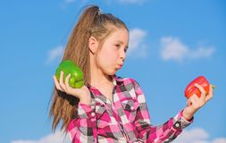Vegetarian concept. Which pepper would you pick. Kid girl hold red and green peppers sky background. Child presenting. Kinds of pepper. Kid hold ripe pepper stock image
