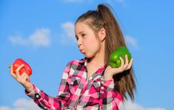 Vegetarian concept. Which pepper would you pick. Kid girl hold red and green peppers sky background. Child presenting. Kinds of pepper. Kid hold ripe pepper stock images