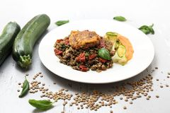 Vegetarian cooking. Colorful vegetable meatless dish. Boiled lentils with carrot puree and grilled zucchini royalty free stock photos