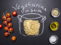 Vegetarian cooking pasta, painted pot, cherry tomatoes, Oil and seasonings wooden rustic background top view Stock Photos