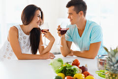 Vegetarian couple drinking red wine in the kitchen Stock Photos