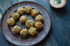 Vegetarian croquettes of potatoes and cabbage with sauce, vegetables and herbs. Packed in parchment. Tasty and satisfying. Dark stock images