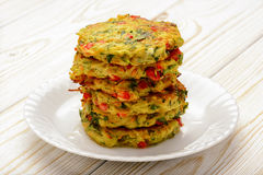 Vegetarian cuisine - vegetable fritters (with potatoes, carrot, zucchini, paprika and parsley). Vegetarian cuisine - vegetable fritters (with potatoes, carrot stock photography