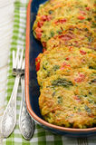 Vegetarian cuisine - vegetable fritters (with potatoes, carrot, zucchini, paprika and parsley). Vegetarian cuisine - vegetable fritters (with potatoes, carrot stock photo